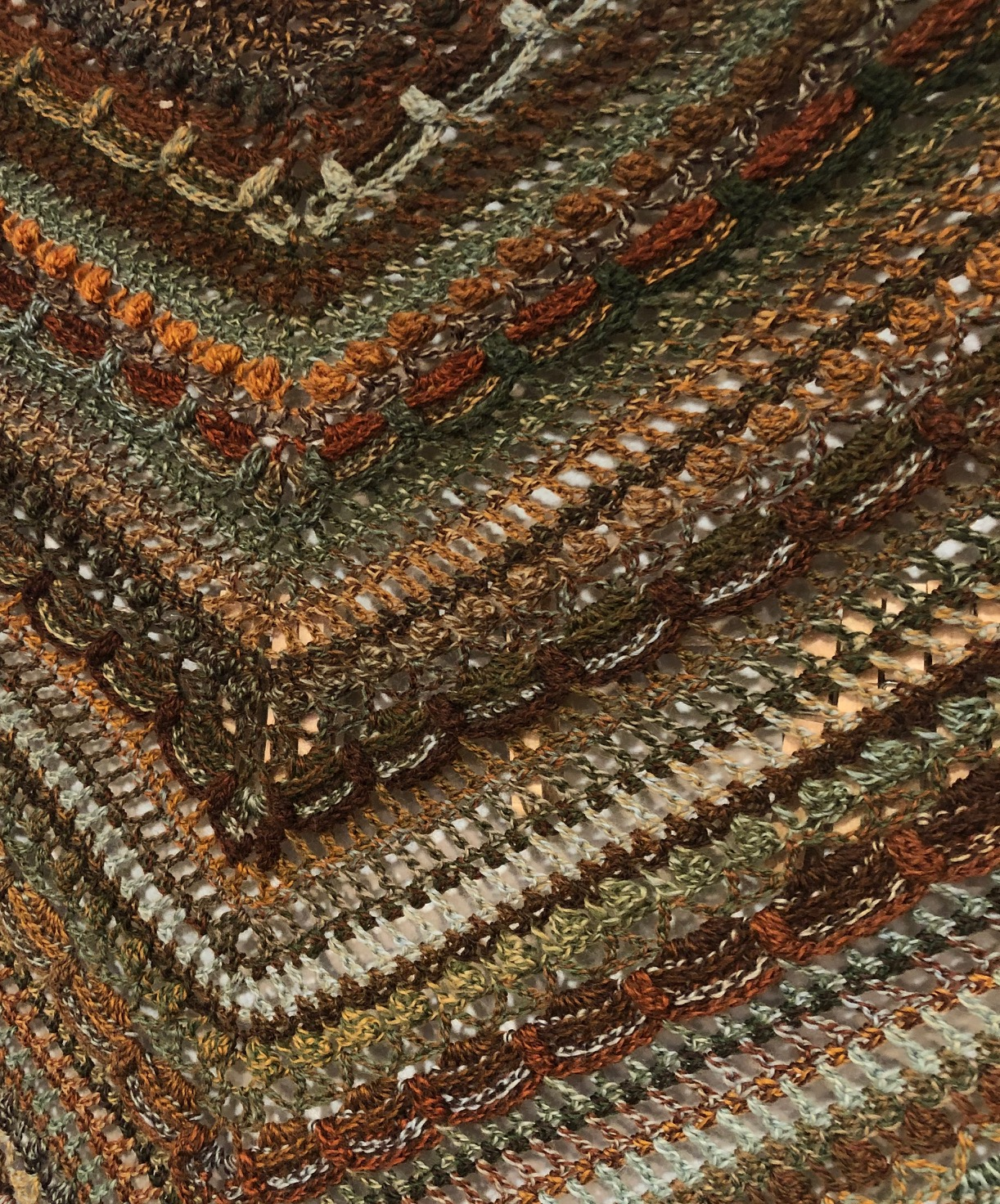 close-up view of crocheted shawl in browns and fall colors